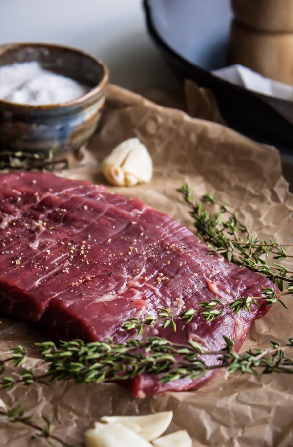 Raw Flank Steak Seasoned with Salt and Pepper