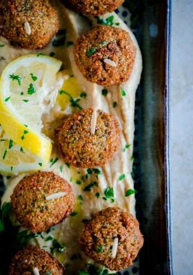 Falafel Bites with Hummus. Bite-sized fried falafel served on toothpicks with lemon twist hummus!