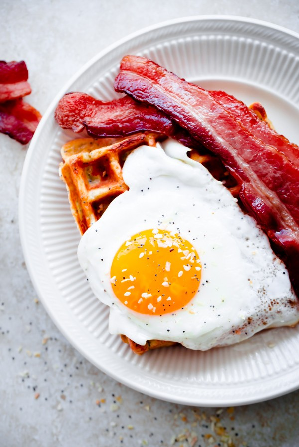 Everything Bagel Breakfast Waffles. Topped with sunny-side eggs and crispy bacon!