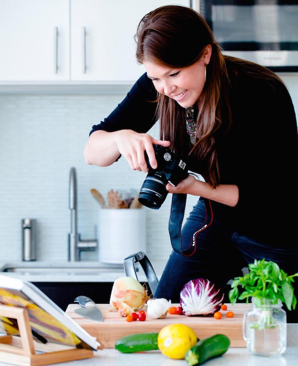 Woman Photographing A Recipe In a Kitchen
