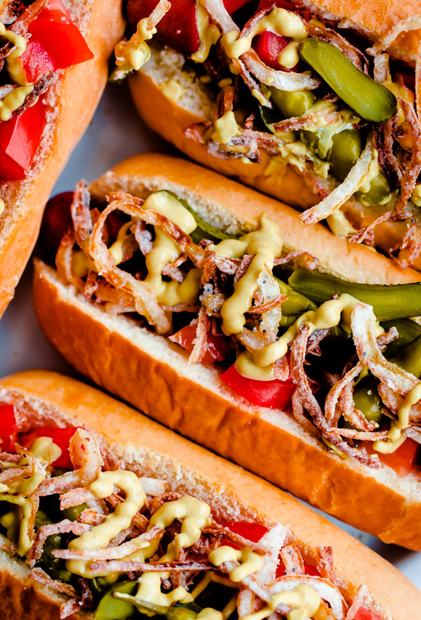 Fancy Chicago-Style Hot Dogs topped with celery salt fried onions, Dijon mustard, cornichon, spicy sport peppers, and chopped tomato! Insanely delicious and easy tailgating food.