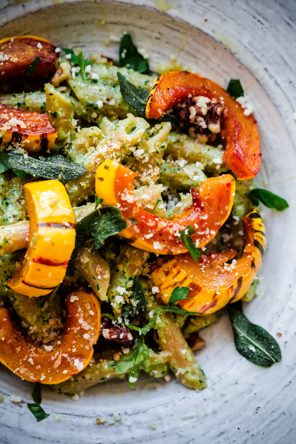 Walnut Sage Pesto Pasta - Whole wheat pasta is tossed with homemade walnut-sage pesto and topped with roasted delicata squash! This vegetarian dish comes together quickly, but is elegant enough to be served for special occasions. #recipe #pasta #vegetarian #sage #pesto #roastedsquash #abeautifulplate