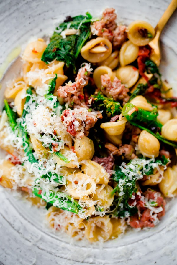 Orecchiette pasta tossed with Italian sausage, broccoli rabe, sun-dried tomatoes, and kalamata olives. This spicy pasta main course can be thrown together in less than 30 minutes and is one of my favorite weeknight pasta recipes.