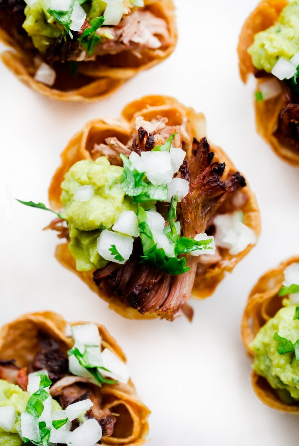 Slow Cooker Carnitas Taco Bites - mini tortilla cups filled with crockpot carnitas and topped with guacamole, onion, and cilantro! Perfect for game day weekend!