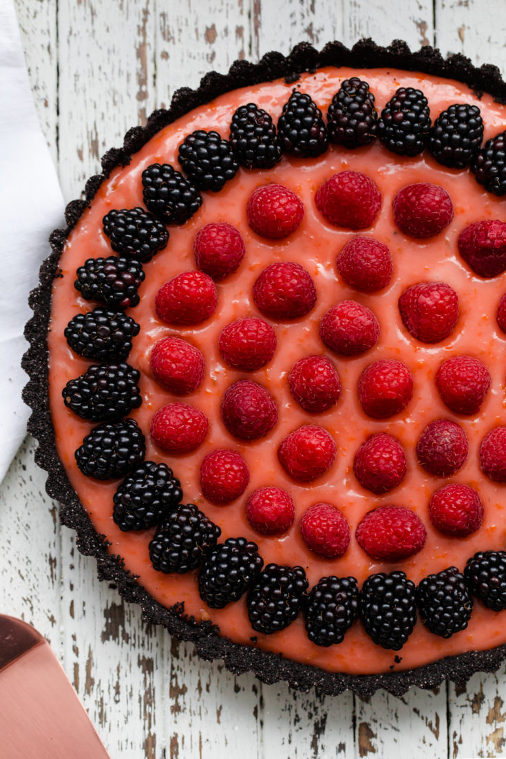 Triple citrus tart with chocolate crust and berries. This elegant tart is made with a dark chocolate wafer crust and filled with blood orange, lemon, and lime curd.  #abeautifulplate #curd #bloodorange #berries #dessert #tart #recipe