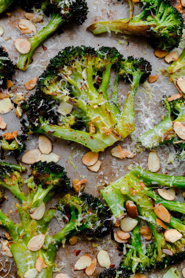 Crack Broccoli - roasted broccoli tossed with sliced toasted almonds, red pepper flakes, garlic, lemon juice, and aged pecorino cheese. You won't be able to stop eating this delicious roasted broccoli side dish! #broccoli #roastedbroccoli #sidedish #recipe #abeautifulplate #glutenfree #vegetarian #keto