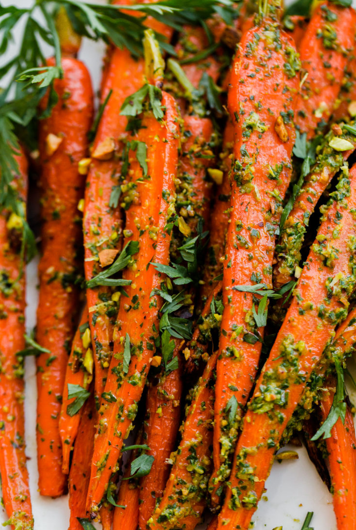 Roasted Carrots with Carrot Top-Pistachio Pesto. This delicious vegan side dish is packed with flavor! #vegan #roastedcarrots #recipe #abeautifulplate
