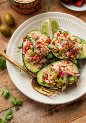 Italian Tuna Avocado Boats - fresh tuna salad made with Bella Portofino extra virgin olive oil packed yellowfin tuna, olives, sundried tomatoes, parsley, and lime served in avocado boats. An easy, healthy, dairy free, gluten free, and paleo friendly recipe!