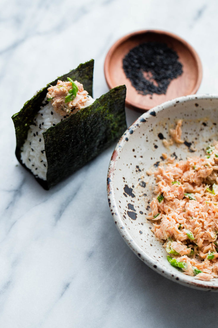Learn how to make homemade nigiri with this simple recipe! This spicy tuna onigiri version is filled with a simple filling of canned olive oil packed tuna, mayonnaise, sriracha, rice vinegar, and scallion. #onigiri #japanese #abeautifulplate #tuna #recipe #snack #glutenfree