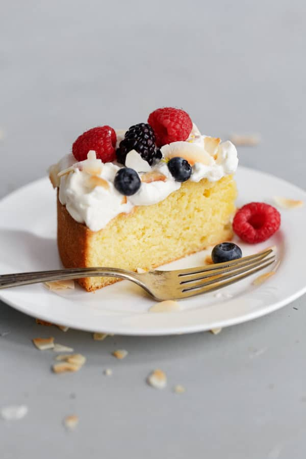 Slice of Lemon Coconut Cake with Cream and Berries