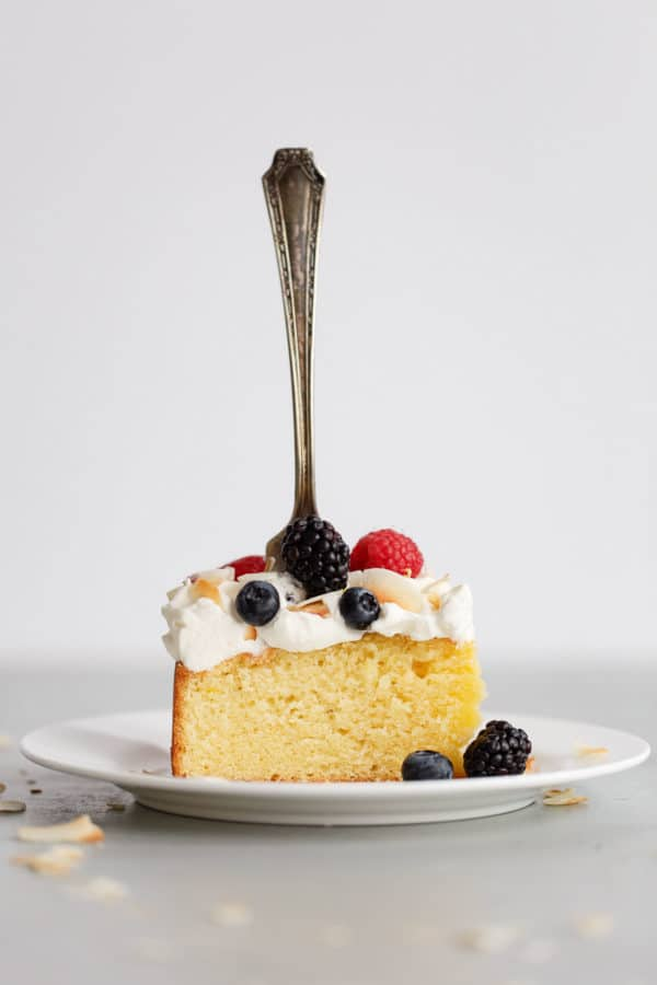 Slice of Lemon Coconut Cake with Whipped Cream Frosting and Berries