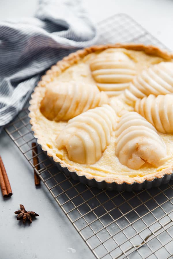 Pear Frangipane Tart - this classic French poached pear tart recipe is made with a sweet tart dough and filled with poached pears and frangipane (almond cream). This tart is delicious and is wonderful served on Thanksgiving or over the holiday season! Top with powdered sugar or apricot glaze. #tart #recipe #abeautifulplate #pear #frangipane #poached #French #dessert #pastry