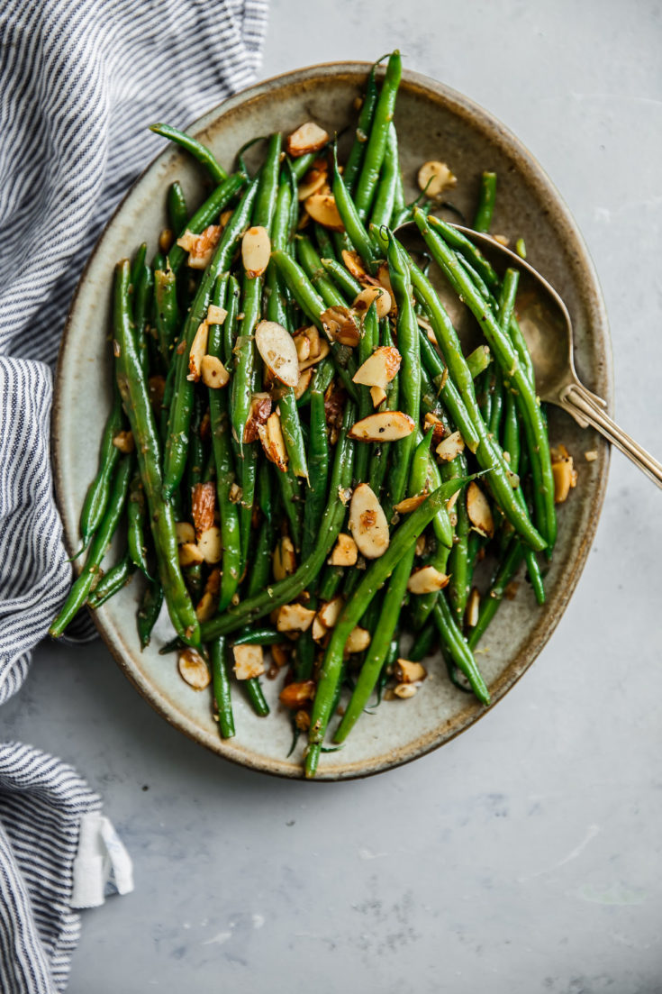 Green Beans Almondine - this classic French recipe of green beans with almonds has been elevated with sautéed shallots and garlic. Lemon zest, and lemon juice add brightness to each bite. This elegant vegetable recipe and side dish comes together quickly and is great for the holidays and pairs well with everything!  #vegetables #sidedish #recipe #greenbeans #almonds #lemon #vegetarian #glutenfree