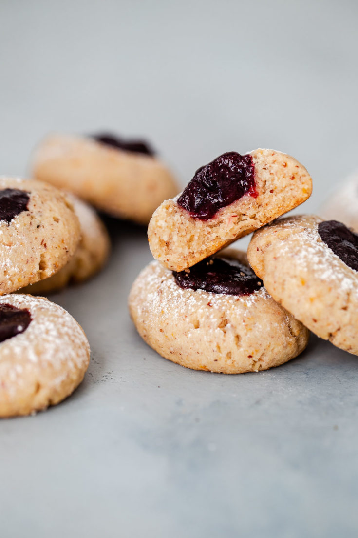 Buttery hazelnut thumbprint cookies filled with a soft berry jam center. These little cookies are easy to make, flavorful, andwould make a lovely last-minute addition to your holiday table!#thumbprint #cookie #christmas #berry #recipe #abeautifulplate