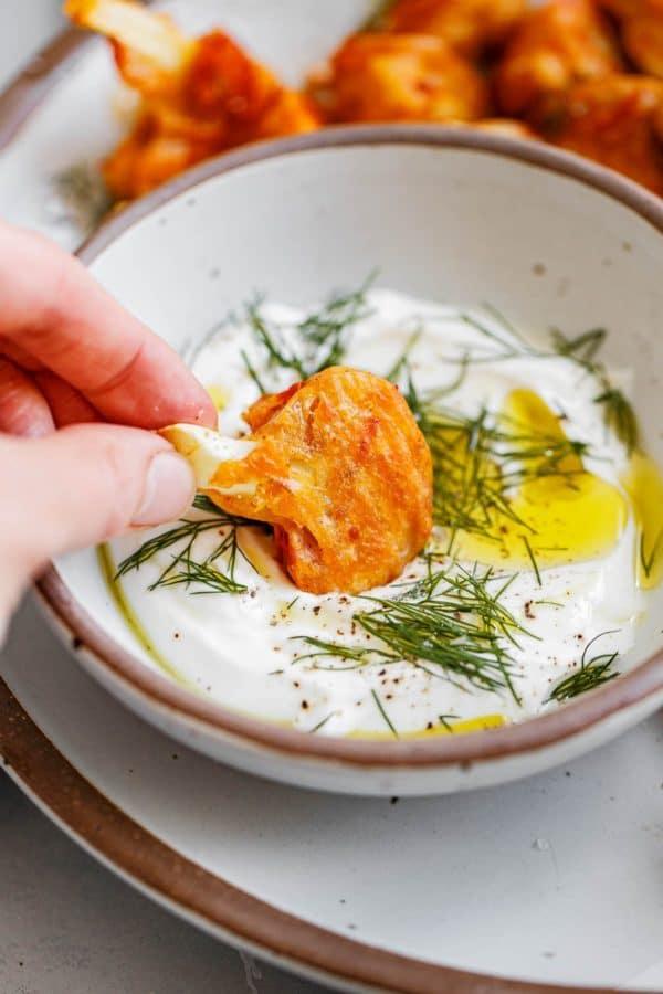 Hand Dipping Buffalo Cauliflower into Yogurt Sauce