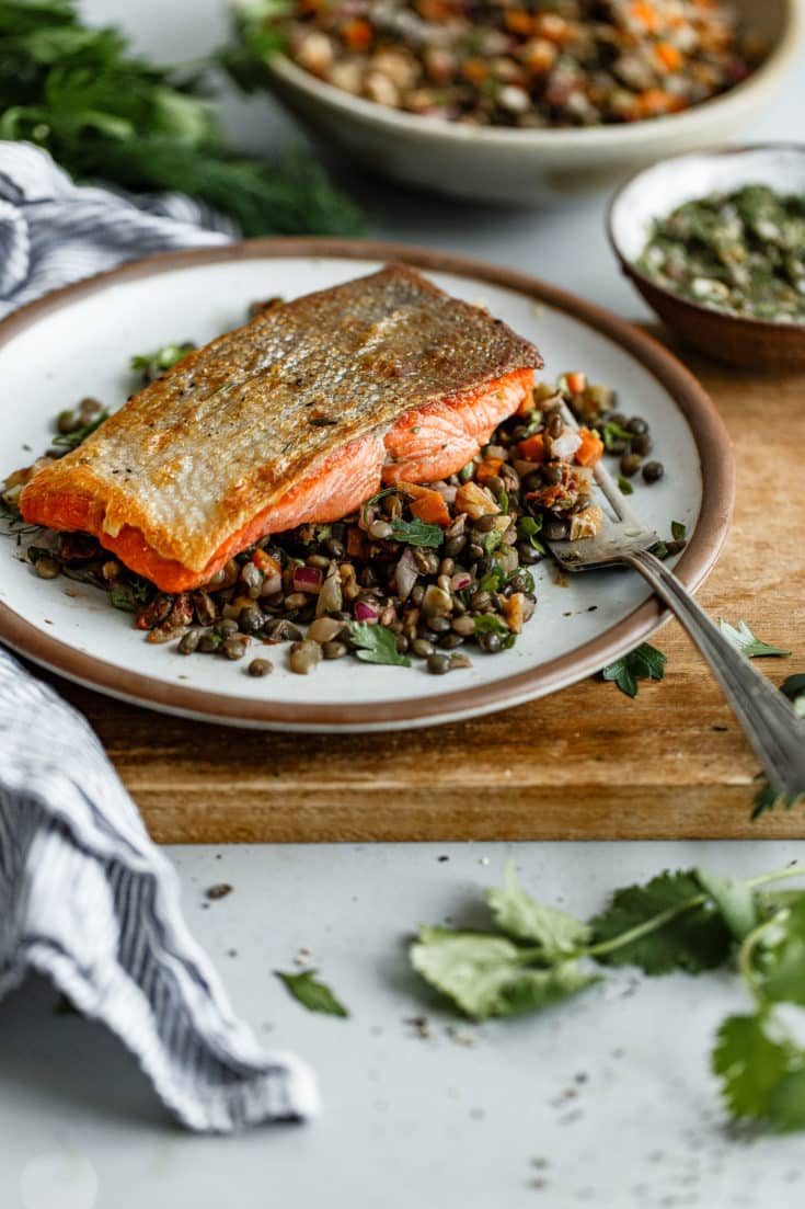 Pan Seared Salmon with Lentils - crispy pan seared salmon topped with a zesty caper herb vinaigrette and served alongside a flavorful French lentil salad. #sponsored #salmon #lentils #abeautifulplate #recipe #healthy #dinner #glutenfree #dairyfree