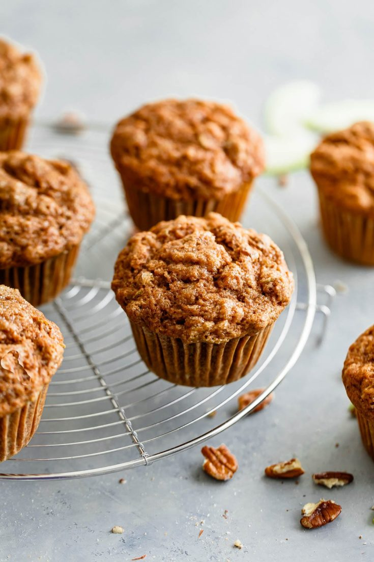 Whole Wheat Apple Cinnamon Muffins get their fluffy and moist texture from the addition of buttermilk, grated apple, and avocado oil. Lightly sweetened with coconut sugar, infused with ground cinnamon, and studded with chopped pecans, this whole wheat muffin recipe is sure to be a hit during the fall season! Sponsored by Bob's Red Mill. #abeautifulplate #muffin #recipe #apple #cinnamon #wholewheat