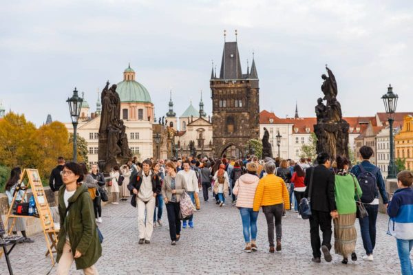 People walking across Charles Bridge in Prague