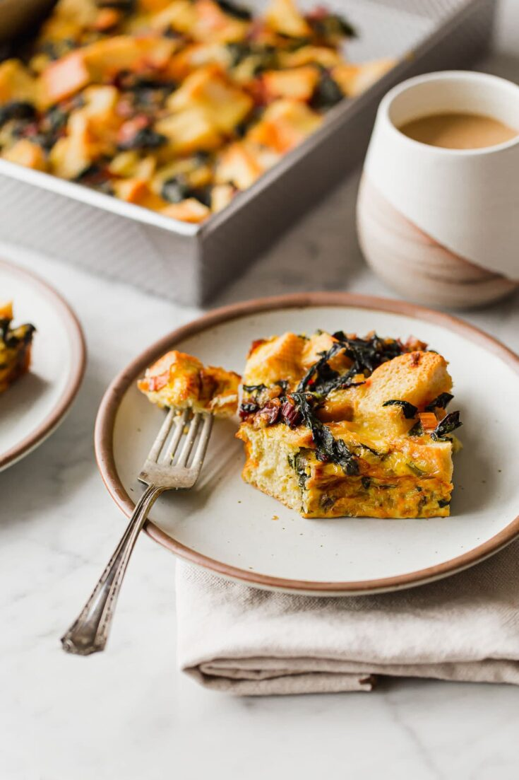 Overnight Breakfast Strata - cheesy, pillowy, and deeply satisfying, this vegetarian breakfast casserole is wonderful any time of year, but particularly ideal for holiday entertaining. #holiday #entertaining #recipe #abeautifulplate #eggs #casserole #chard #cheese #easyrecipes #vegetarian