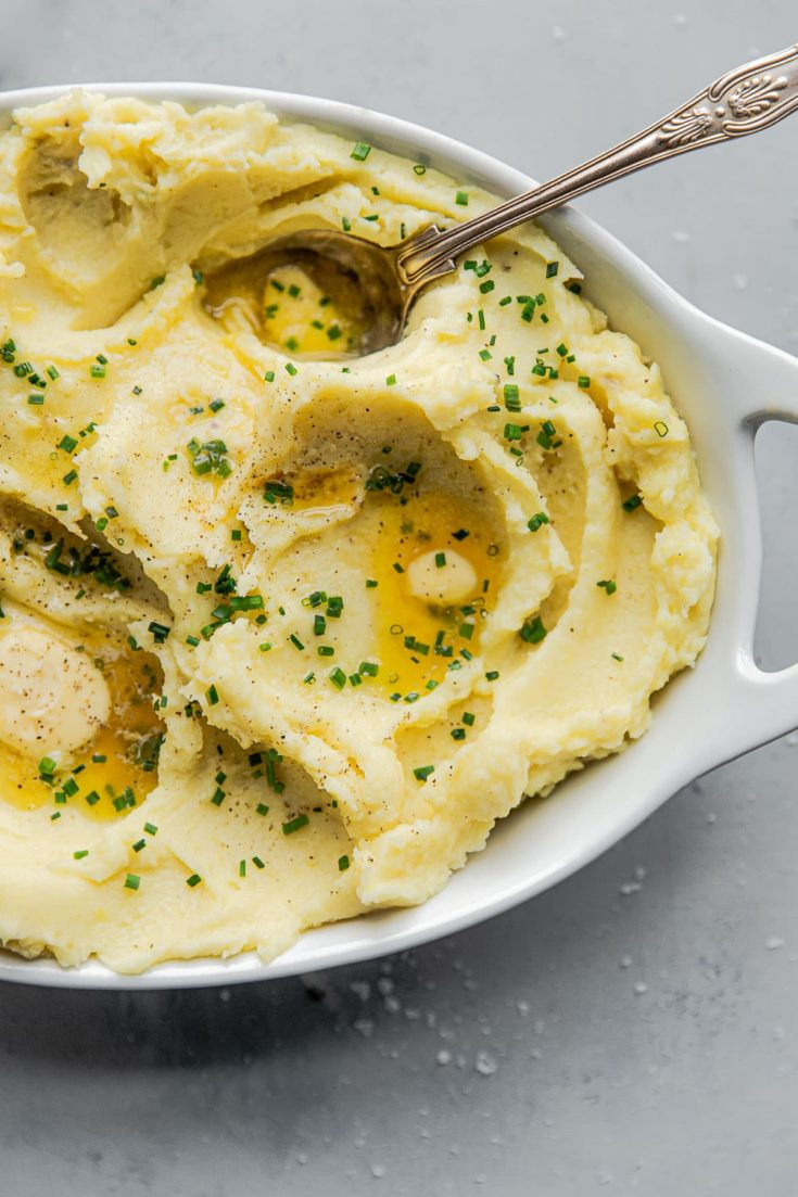 Classic Yukon Gold Mashed Potatoes prepared with heavy cream, unsalted butter, salt, pepper, and garnished with chives. These simple mashed potatoes are perfect for Thanksgiving and holidays and pair well with just about everything. #thanksgiving #holiday #potatoes #abeautifulplate #Yukongold #recipe #sidedish #easyrecipes