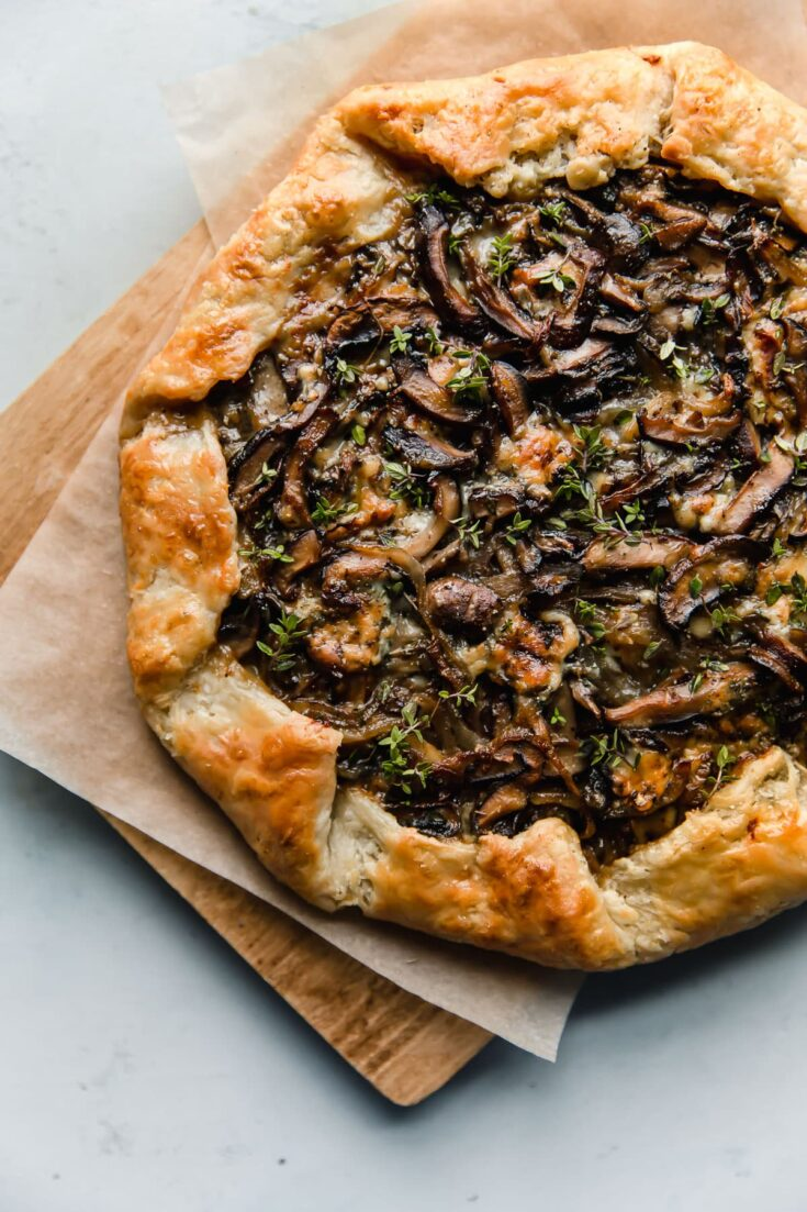 Mushroom Galette - rustic and flavorful, this cremini and shiitake mushroom galette is filled with sharp blue cheese and wrapped in a flaky sour cream pastry dough. This rustic mushroom tart is great for entertaining!#galette #mushroom #tart #cremini #shiitake #recipe #abeautifulplate