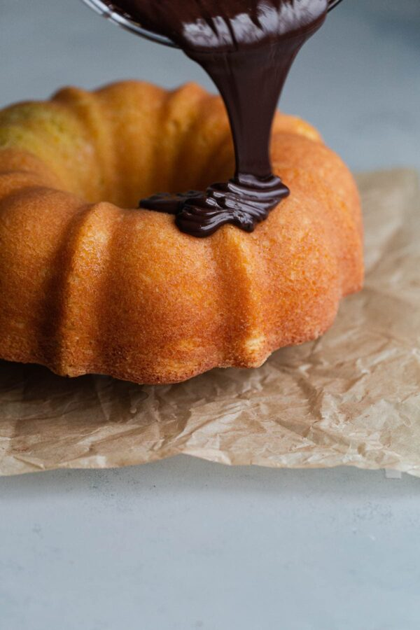 Chocolate Glaze Being Poured on Orange Bundt Cake