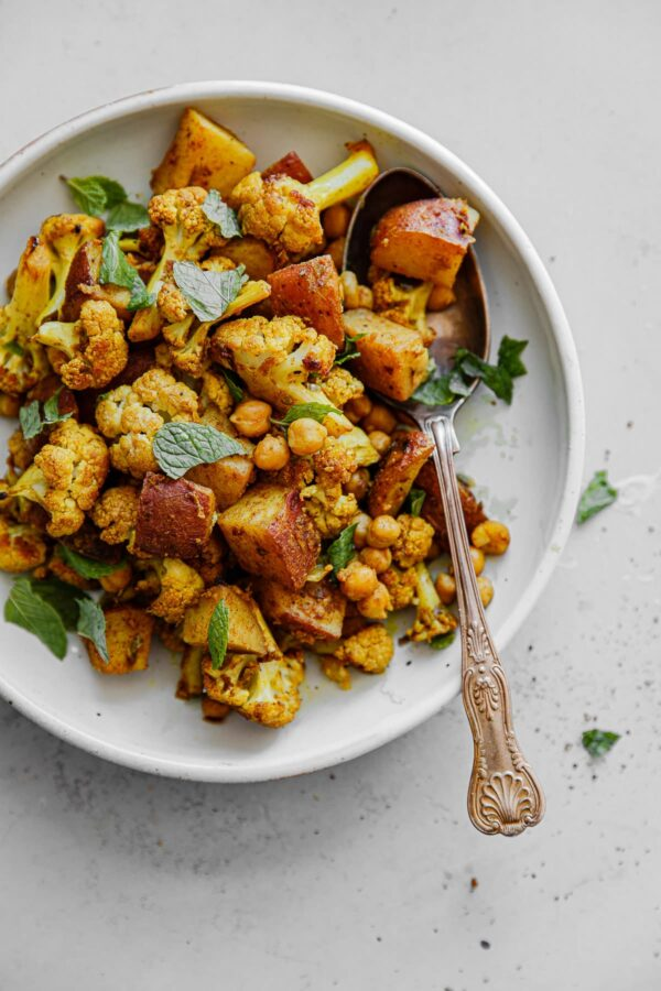 Sheet Pan Roasted Cauliflower Chickpea Curry on Plater with Serving Spoon