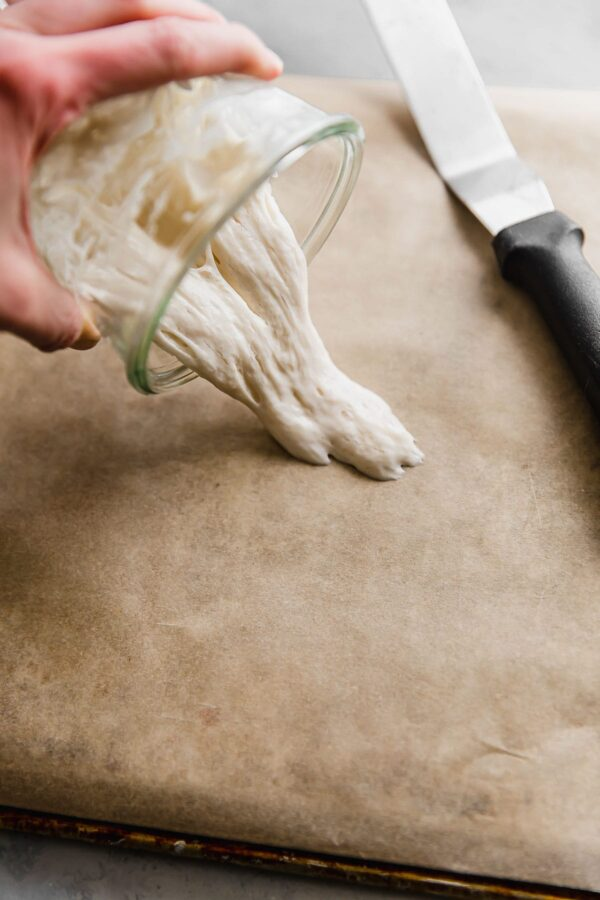 pouring sourdough starter onto parchment paper for drying